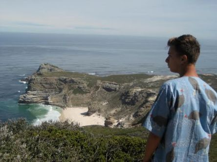 HSU student standing at Cape of Good Hope in South Africa looking at the ocean and lower beach